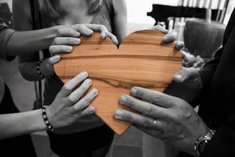A group of people holding a wooden heart.